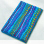 multi color novelty bath rug with fun colored stripes running over a solid background of either black, white, berry, navy or turquoise